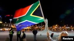 ក្មេងស្រីនេះ កាន់ទង់ជាតិនៃប្រទេសអាហ្វ្រិកខាងត្បូង គ្រាដែលពលរដ្ឋនៃប្រទេសនេះកាន់មរណទុក្ខនៃការស្លាប់របស់អតីតប្រធានាធិបតីលោក Nelson Mandela នៅក្រៅសាលាក្រុងក្នុងទីក្រុង Cape Town។