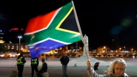 A girl holds a South African national flag as people mourn the death of former President Nelson Mandela outside Cape Town City Hall, where Mandela made his first speech after his release from his 27-year incarceration, Dec. 6, 2013.
