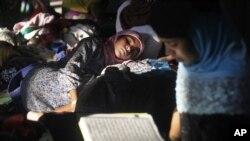 Des migrantes lisent le coran dans l'ile de Sumatra, Indonésie, 13 mai 2015.