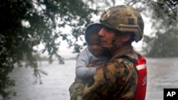 Član Nacionalne garde Severne Karoline, Nik Mjuhar, evakuiše dete iz kuće poplavljene u uraganu Florens.
