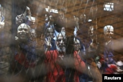 Muslim Brotherhood's Supreme Guide Mohamed Badie (C) waves with the Rabaa sign, symbolizing support for the Muslim Brotherhood, with other brotherhood members at a court in the outskirts of Cairo, May 16, 2015.