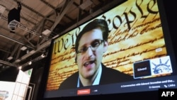 "FILE - NSA whistleblower Edward Snowden speaks via videoconference at the ""Virtual Conversation With Edward Snowden"" during the 2014 SXSW Music, Film + Interactive Festival at the Austin Convention Center, March 10, 2014."