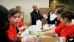 Democratic presidential candidate Sen. Cory Booker, center, D-N.J., tours the Three Square food bank Thursday, Dec. 19, 2019, in Las Vegas. (AP Photo/John Locher)