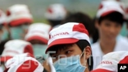 Chinese factory workers wearing masks gather during a strike at an auto parts plant of Honda in Foshan city, south Chinas Guangdong province, 26 May 2010