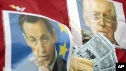 ຜູ້ປະທ້ວງຄົນນຶ່ງ ທີ່ກໍາເງິນປອມ ທີ່ມີຮູບຂອງນາຍົກລັດຖະມົນຕີອີຕາລີ ທ່ານ Mario Monti ລີ້ຢູ່ລະຫວ່າງກາງຮູບ ຂອງທ່ານ Monti ກັບຮູບຂອງປະທານາທິບໍດີຝຣັ່ງ ທ່ານ Nicholas Sarkozy(ຊ້າຍ) ໃນລະຫວ່າງການປະທ້ວງ ຕໍ່ຕ້ານການປະຕິຮູບທາງດ້ານເສດຖະກິດ ຢູ່ສະຖານີລົດໄຟ Termini ໃນກຸງ Rome