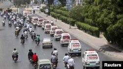 Barisan ambulan membawa jenazah korban serangan bis ke lokasi pemakaman di Karachi, Pakistan (14/5).