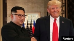 Presiden AS Donald Trump (kanan) dan pemimpin Korea Utara Kim Jong Un dalam pertemuan pertama di Singapura, 12 Juni 2018.