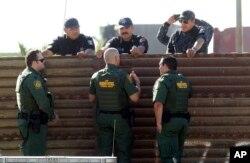 FILE - U.S. Customs and Border Protection's acting deputy commissioner Ronald Vitiello, center foreground, and two other CBP agents, talk over the primary fence to their Mexican Federal Police counterparts in Tijuana, Mexico, Oct. 26, 2017, in San Diego.