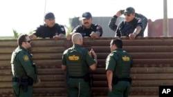 Ronald Vitiello, sous-commissaire par intérim de la Protection des frontières, et deux autres agents, échangent avec leurs homologues de la police fédérale mexicaine à Tijuana, au Mexique, le 26 octobre 2017.
