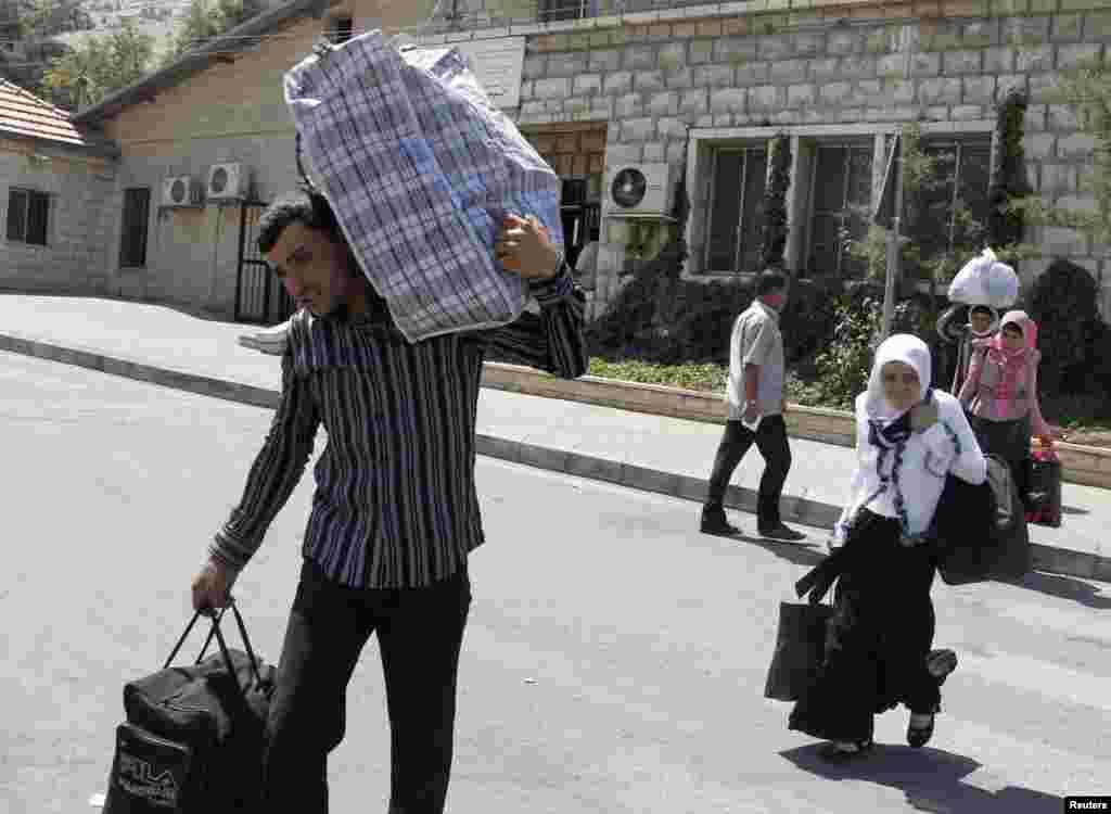 Suriyalik qochqinlar Livan-Suriya chegarasidan o'tmoqda, 20-iyul, 2012-yil.