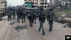 FILE - This Tuesday, Jan 12, 2016, file photo released by the Syrian official news agency SANA, shows Syrian government troops and allied militiamen walk inside the key town of Salma in Latakia province, Syria.