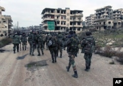 FILE - Syrian government troops and allied militiamen walk inside the key town of Salma in Latakia province, Syria, Jan 12, 2016.