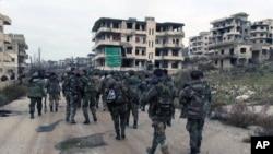 Quân đội chính phủ Syria song hành cùng dân quân đồng minh bên trong thị trấn Salma của tỉnh Latakia, Syria. Ảnh do hãng tin chính thức của Syria SANA đăng tải hôm 12/1/2016.