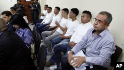 FILE - Men accused in the killing prize-winning Honduran indigenous and environmental rights activist Berta Caceres sit in a court room in Tegucigalpa, Honduras, Sept. 17, 2018.
