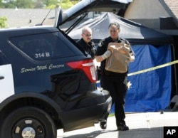 Sacramento sheriff's deputies carry evidence taken from the home of suspect Joseph DeAngelo to a sheriff's vehicle, April 26, 2018, in Citrus Heights, Calif. DeAngelo, 72, was taken into custody, Tuesday, on suspicion of committing at least 12 slayings and a number of rapes.