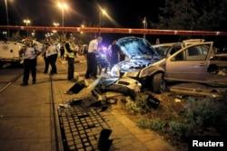 Israeli policemen inspect a car wreck in Jerusalem, Oct. 22, 2014.