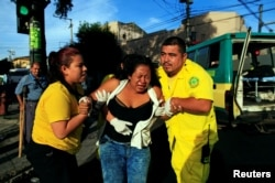 Rescuers Maria Martinez, left, and Renato Landaverde help a woman who was hit by a bus in San Salvador, El Salvador, July 17, 2016.