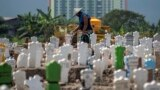 A worker pours water on newly planted flowers at a burial site for victims of the COVID-19 coronavirus at Keputih cemetery in Surabaya, East Java on July 15, 2020. (Photo by JUNI KRISWANTO / AFP)