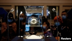 Visitors look at Moon samples from China's lunar exploration program Chang'e-5 Mission during an exhibition at the National Museum in Beijing, China March 3, 2021. (REUTERS/Tingshu Wang)
