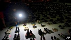 FILE - A child shines a light on hundreds of shoes at a memorial for those killed by Hurricane Maria, in front of the Puerto Rico Capitol in San Juan., June 1, 2018.