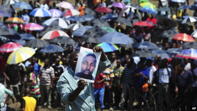 A man holds an image of an un-named alleged victim of the recent mining violence during a demonstration in Rustenburg, South Africa, October 6, 2012.