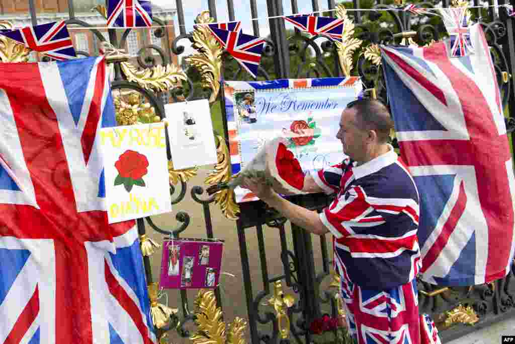 A royal supporter places flowers on the gates of Kensington Palace in London as a tribute to Britain's Princess Diana, marking the 17th anniversary of her death.