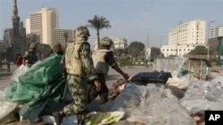 Des soldats égyptiens démontant les tentes des manifestants sur la place Tahrir