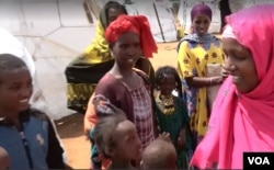 Abdiya Golicha, wearing pink, lives in northern Kenya's Marsabit County and volunteers to help Ethiopian refugees at the Dambala Fachana camp. (D. Gelmo/VOA)