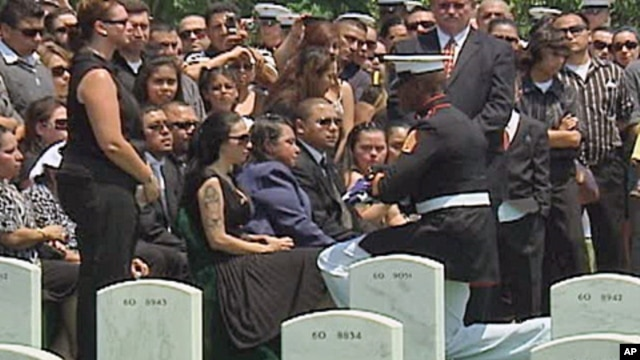 A marine presents the widow with a folded American flag.