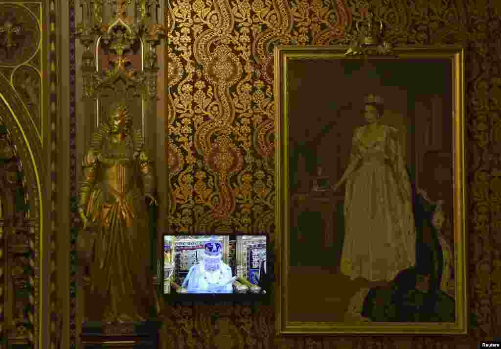 Britain's Queen Elizabeth is seen on a TV monitor as she delivers her speech during the opening of Parliament in the House of Lords, at the Palace of Westminster in London.