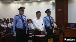 بوژلائی کمرہ عدالت میں کھڑے ہیں