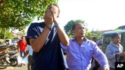 Polisi menggiring Tommy Schaefer (kiri) untuk dibawa ke kantor polisi di Denpasar untuk diinterogasi (13/8). (AP/Firdia Lisnawati)