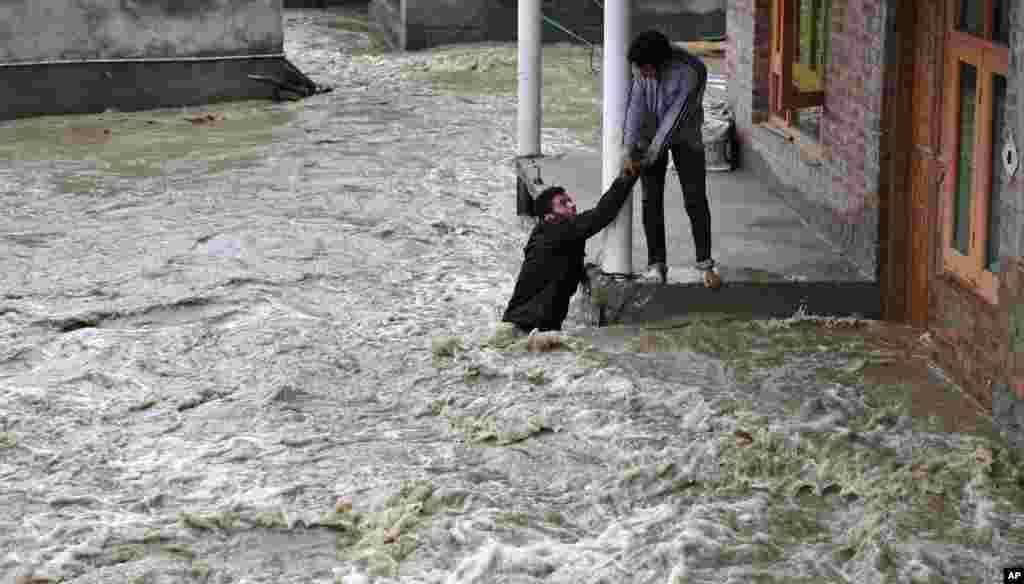 A Kashmiri man helps a local evacuate from a flood affected area in Srinagar.