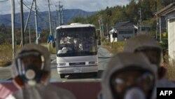 Các giới chức và phóng viên Nhật Bản mặc đồ bảo hộ ngồi trên xe buýt chạy qua vùng bị nhiễm xạ trên đường đến nhà máy điện hạt nhân Fukushima Dai-ichi ở Okuma, Nhật Bản, ngày 12 tháng 11, 2011
