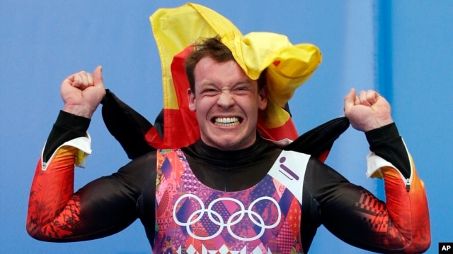 Felix Loch of Germany jumps onto the podium after he won the gold medal during the men's singles luge final at the 2014 Winter Olympics, Feb. 9, 2014, in Krasnaya Polyana, Russia.