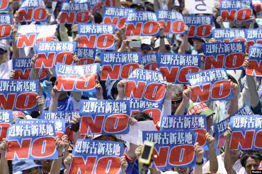 Protesters raise placards during a rally at a baseball stadium in the prefectural capital Naha on Japan's southern island of Okinawa to oppose the transfer of a key U.S. military base within the prefecture, in this photo taken by Kyodo.