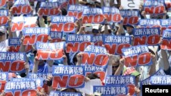 Protesters raise placards during a rally to oppose the transfer of a key U.S. military base within the prefecture, at a baseball stadium in the prefectural capital Naha on Japan's southern island of Okinawa, in this photo taken by Kyodo May 17, 2015. The Navy has received increased pressure in Okinawa where residents are calling for the removal of U.S. bases. American military arrests help the Japanese argument.