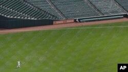El jugador de los Medias Blancas de Chicago, Delmon Young, lanza la pelota en el partido sin público que juega su equipo contra los Orioles.