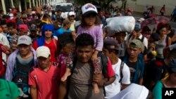 El martes 16 de octubre, en Chiquimila, Guatemala, un migrante hondureño lleva a una niña pequeña sobre sus hombros como parte de la caravana que se dirige a EE. UU.