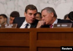 Senate Intelligence Committee ranking member Mark Warner (D-VA) (L) talks with Chairman Richard Burr (R-NC) during former FBI Director James Comey's appearance before a Senate Intelligence Committee hearing on Russia's alleged interference in the 2016 U.S. presidential election on Capitol Hill.