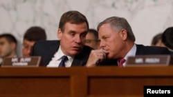 Senate Intelligence Committee ranking member Mark Warner (D-VA) (L) talks with Chairman Richard Burr (R-NC) during former FBI Director James Comey's appearance before a Senate Intelligence Committee hearing on Russia's alleged interference in the 2016 U.S electrion, June 8, 2018.