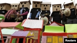FILE - People wear house models during a march on World Habitat Day in Phnom Penh, Oct. 5, 2015. Former residents of Boeung Kak Lake, Borei Keila neighbourhood and other communities affected by private corporation developers called on the Cambodian government to stop evicting them from their homes.