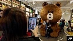 Turis berfoto dengan karakter beruang Line di toko cenderamata Line Friends di Seoul. (AP/Lee Jin-man)