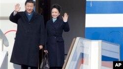 Presiden China Xi Jinping dan ibu negara Peng Liyuan saat tiba di bandar udara Vnukovo II, di luar kota Moskow. (AP/Ivan Sekretarev)