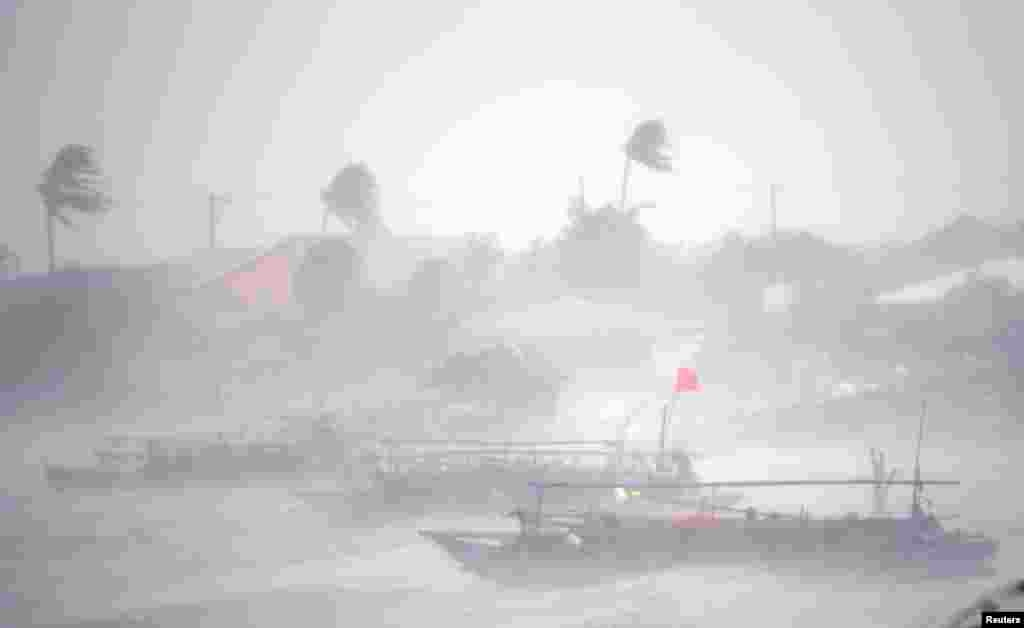 Fishing boats amid heavy winds and rain brought by Typhoon Rammasun (locally named Glenda) as it hit the town of Imus, Cavite southwest of Manila, Philippines.