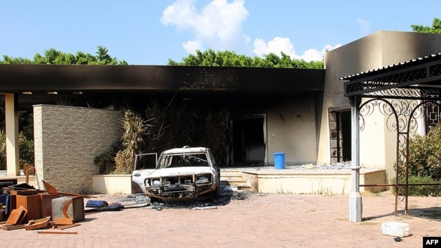 This file photo taken on September 12, 2012 shows a burnt house and a car inside the US embassy compound in Benghazi following an overnight attack on the building.
