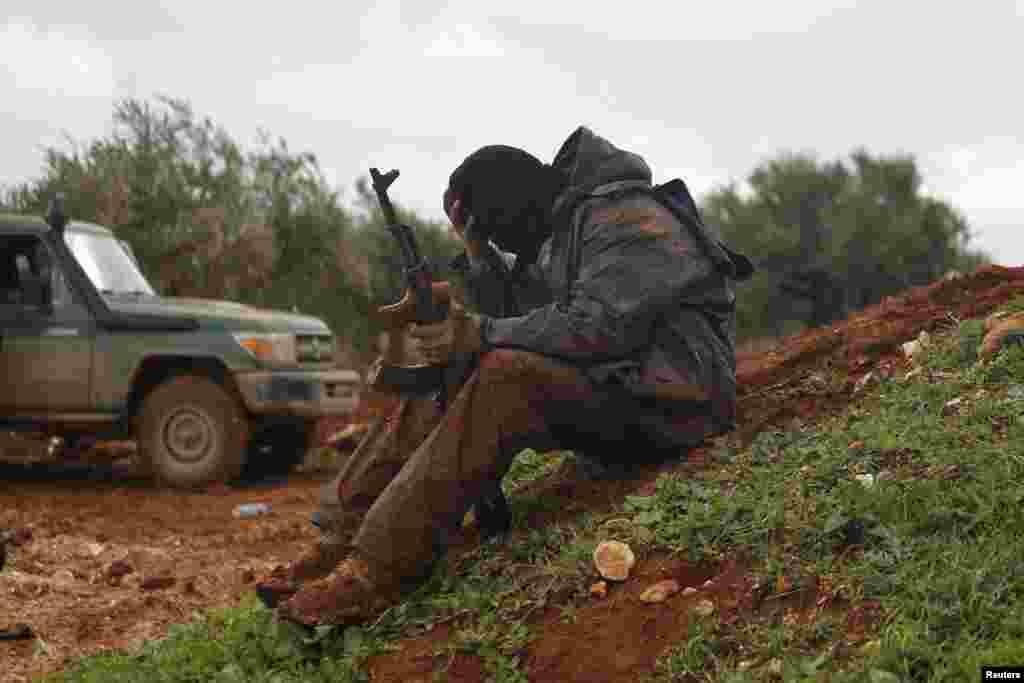 Một chiến binh nổi dậy của nhóm al-Jabha al-Shamiya (Mặt trận Shamiya) lấm lem bùn ngồi gần tiền tuyến trong làng Bashkuwi, phía bắc thành phố Aleppo, Syria.