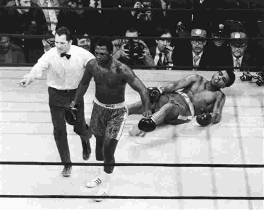 FILE- This March 8, 1971, file photo, shows boxer Joe Frazier being directed to the ropes by referee Arthur Marcante after knocking down Muhammad Ali during the 15th round of the title bout at Madison Square Garden in New York. Former heavyweight champion