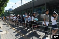 FILE - People line up for visa applications outside the US embassy in Beijing on July 26, 2018.