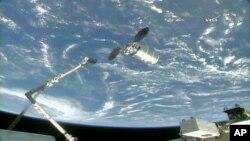El brazo robótico de la Estación Espacial Internacional es extendido para alcanzar la nave de carga Cygnus el martes, 14 de noviembre de 2017 (260 millas) 418 kilómetros sobre la Tierra.